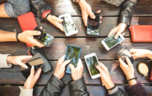 circle of hands holding smartphones