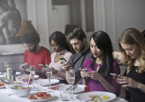 dinner party of people all on their phones, distracted