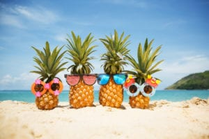 four cute summer pineapples on the beach in funny glasses