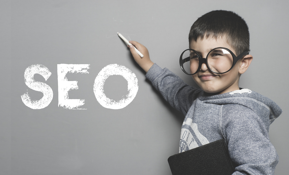 cute kid with a pointer at the word SEO