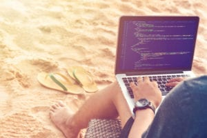coder on the beach with laptop
