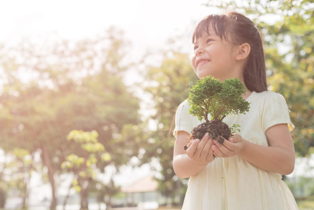earth day, cute girl holding baby tree
